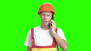 Construction worker talking on cell phone. Mature foreman talking on mobile phone on chroma key background. Confident foreman with mobile phone.
