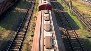 Container freight train with many cargo wagons transporting. Top aerial view.