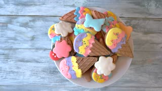 Cookies with colorful frosting, top view. Tasty ice cream cone cookies on wooden background. Ideas of delicious desserts. Easy dessert for kids birthday.