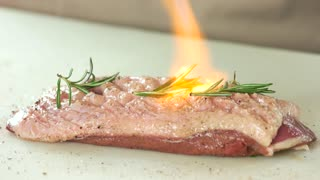 Cooking meat with culinary torch. Duck breast with rosemary.