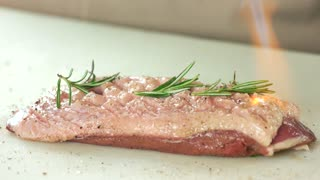 Cooking poultry with culinary torch. Meat with rosemary.