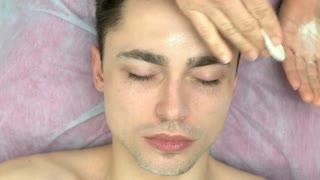 Cosmetician applying talcum powder, face. Young caucasian man, cosmetology.