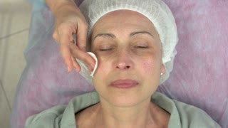 Cosmetician cleaning face, mature woman. Hand using cotton pad. Facial toners for dry skin.