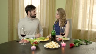 Couple at dinner table hugging. Smiling people indoors. Dating etiquette for men.