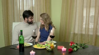 Couple at dinner table laughing. Young woman hugging man. What is romance.