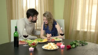 Couple eating spaghetti and laughing. Cheerful caucasian man and woman. Love is funny.