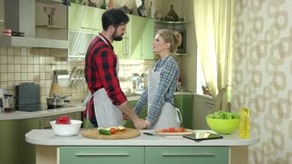 Couple holding hands, kitchen. Woman smiling and kissing man. Love, health and happiness.