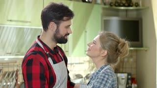 Couple hugging in the kitchen. Woman kisses man on cheek.