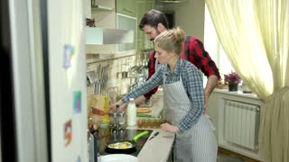Couple in kitchen frying eggs. Young people laughing indoors.