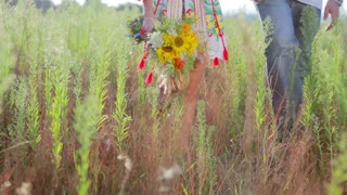 Couple in love walking on the field. Guy present his beloved a bouquet of wildflowers. A date in nature. Lovers walk in the countryside.