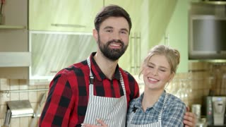 Couple in the kitchen smiling. Happy young man and woman.