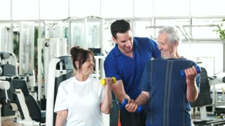 Couple of seniors lifting dumbbells at gym. Friendly personal trainer at a fitness center helping to seniors. Fitness trainer showing thumb up. Benefits of strength training exercises for seniors.