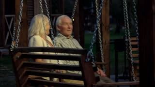 Couple of seniors, porch swing. Woman and man talking. Strong relationship tips.