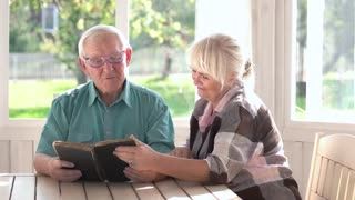 Couple of seniors reading book. Man and woman at table.