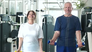 Couple of seniors training at gym. Smiling older people exercising with dumbbells at fitness club. Elderly people and sport.