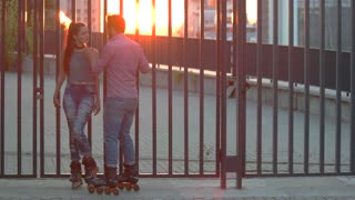 Couple on inline skates. Man touching woman's neck. Date of active people. Whisper in my ear.