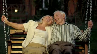 Couple on porch swing. Happy man and woman, evening.