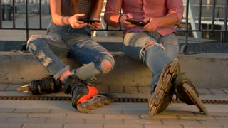 Couple on rollerblades is sitting. Two people playing on phones. Surpass the opponent. Technologies and sport.