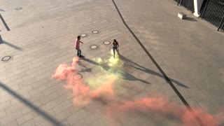 Couple on rollerblades outdoors. Orange and yellow smoke. Colorize this world. Youth chooses sport and health.