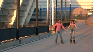 Couple rollerblading and holding hands. Young man and woman outdoor. Good idea for active date. Sport and romance.