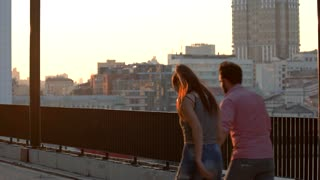 Couple rollerblading at sunset. People on background of city. Great idea for first date. Hold my hand.