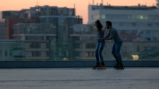Couple rollerblading in the evening. Man holding woman by waist. Learn to keep the balance. Always by your side.