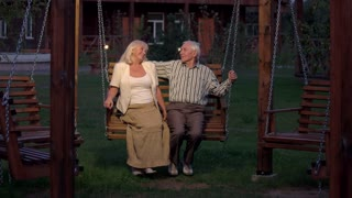 Couple sitting on porch swing. Old man and woman, evening.