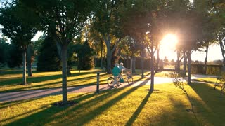 Couple walking and holding bicycle. Park at sunset. Best season for picnics. Our favorite place outside town.