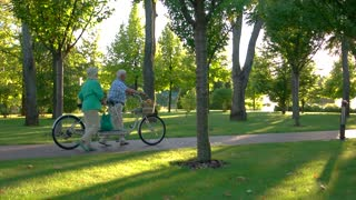 Couple walking with bicycle. Senior people in the park. This place is so familiar. We are almost there.