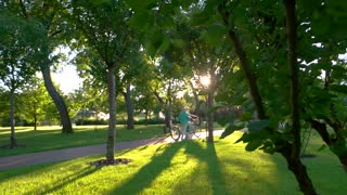 Couple with bike is walking. Senior people outdoors. Admire the beauty around you. One more summer spent together.