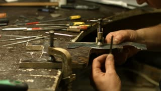 Craftsman creates a template. Template for drawing. Careful work on metal template. Construction of a small workpiece.