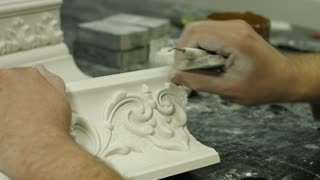 Craftsman picking gypsum ornament. Careful work on gypsum. Picking tiny bits of material. Part of expensive painting frame.