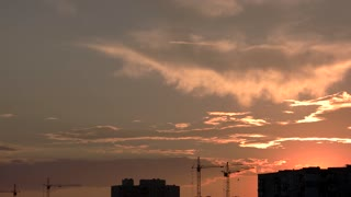 Cranes and buildings, sunset sky. Construction site and clouds. Profitable business ideas.
