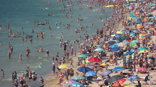 Crowded sunny beach. Many people at seaside. Nice vacation spot.