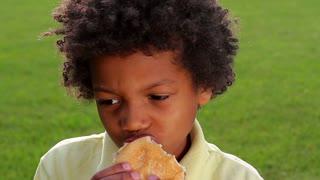 Cute boy is eating big hamburger closeup.