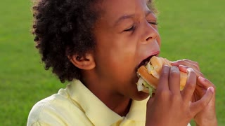 Cute boy is eating big tasty hamburger closeup.