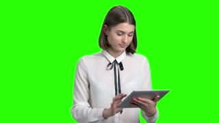 Cute brunette girl using tablet. Portrait of young beautiful woman with device. Green screen hromakey background for keying.