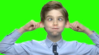 Cute child boy fooling around. Pulling ears and cross eyes. Green hromakey background for keying.