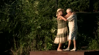 Cute couple of seniors dancing outdoors. Beautiful elderly people near river, summer nature background. The best rest ever.