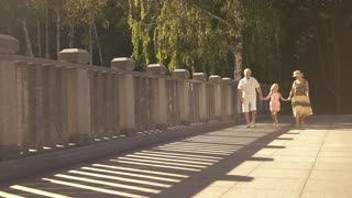 Cute girl walking with grandparents. Beautiful child in dress holding hands with seniors and cheerfully walking on bridge. Happy childhood with grandparents.