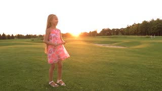 Cute little girl catching a ball. Slow motion beautiful happy child with long hair having fun with ball on green meadow at sunset. Life energy and freedom.
