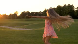 Cute little girl dancing on grass. Adorable child is spinning outdoors. Childhood and freedom.