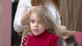 Cute little girl, hair salon. Hands of hairstylist, curling tongs.