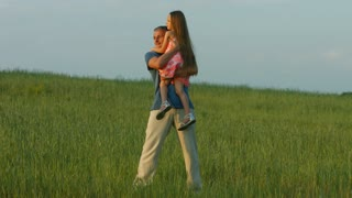 Dad hugs daughter. Father and girl walking on a green meadow.
