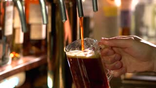 Dark ale overfilling glass, slow-mo. Tap beer overflowing glass and turning off, slow-mo.