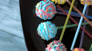 Decorated ball-shaped sweets on sticks. Candies on gray wooden surface. Cake pops from pastry shop.