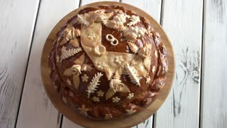 Decorated bread on wooden boards. Baked round loaf of brown color. Pastry for wedding ceremony.