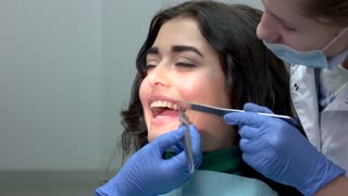 Dentist installing teeth braces. Hands of doctors in gloves. Dental brackets, pros and cons.