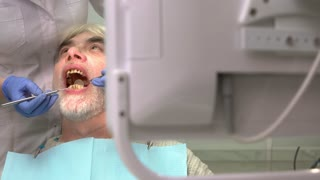 Dentist with mirror examining patient. Man with bad teeth. Benefits of dental insurance.