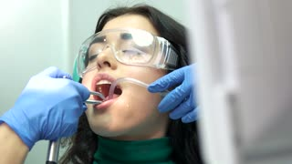 Dentists are working with patient. Woman in safety glasses. Dental procedures in a clinic.